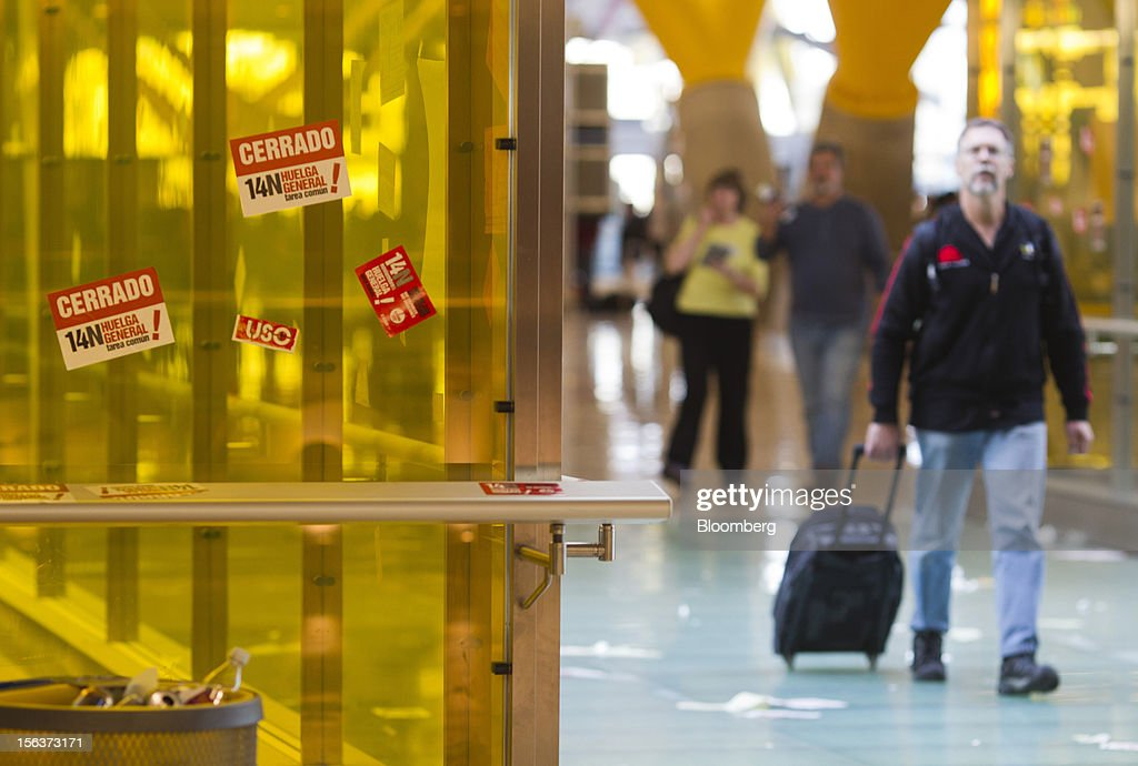 A traveler passes stickers calling for strike action at Madrid airport on the morning of a general strike in Madrid, Spain, on Wednesday, Nov. 14, 2012. Spanish unions today staged their second general strike against Prime Minister Mariano Rajoy as mounting opposition to budget cuts and bank bailouts undermines the 11-month-old government's ability to repair the economy. Photographer: Angel Navarrete/Bloomberg via Getty Images