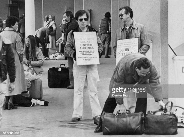 Traveler Picks up his Luggage as two pickets stand near with signs proclaiming United Airlines Strike Ninetysix United flights going through...