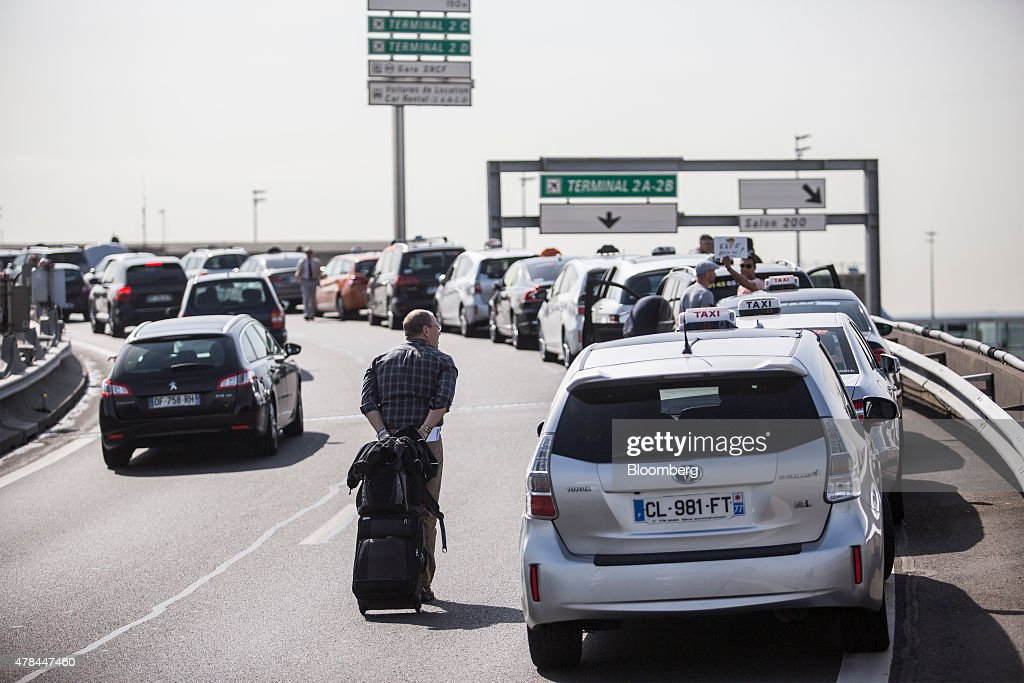 A traveler pulls his luggage past a row of French taxi cabs sat on a road outside Charles de Gaulle airport during a protest against Uber Technologies Inc.'s car sharing service in Roissy, France, on Thursday, June 25, 2015. French taxi drivers are on indefinite nationwide strike as they demand a government crackdown on what they say is Uber's use of unlicensed chauffeurs for its UberPop service. Photographer Balint Porneczi/Bloomberg via Getty Images