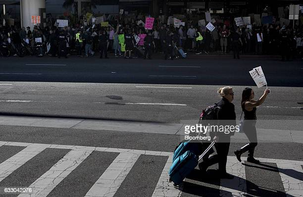 A traveler pulls luggage as demonstrators hold signs outside Los Angeles International Airport protesting against US President Donald Trump's...