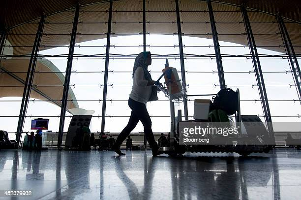 A traveler pushes a buggy near a checkin area at Kuala Lumpur International Airport in Sepang Malaysia on Saturday July 19 2014 Flags in Malaysia...