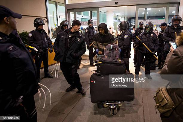 A traveler pushes a luggage cart of luggage past a group of police guarding Terminal 4 at John F Kennedy International Airport during a protest...