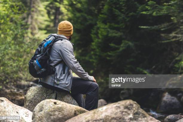 Traveler resting sitting on a rock in the forest