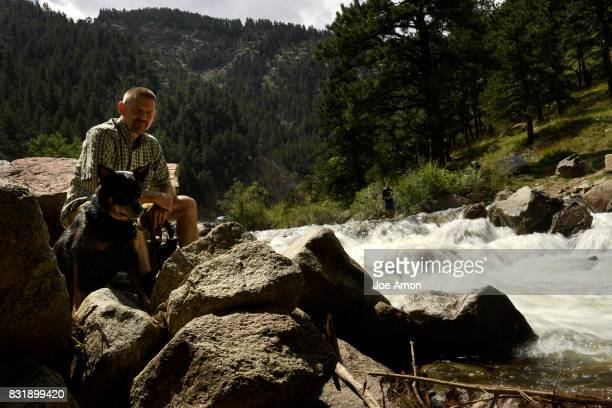 A traveler Richard Kroyer and his Heeler Dillion resting along Boulder Creek in Boulder Canyon while visiting family in the area August 15 2017...
