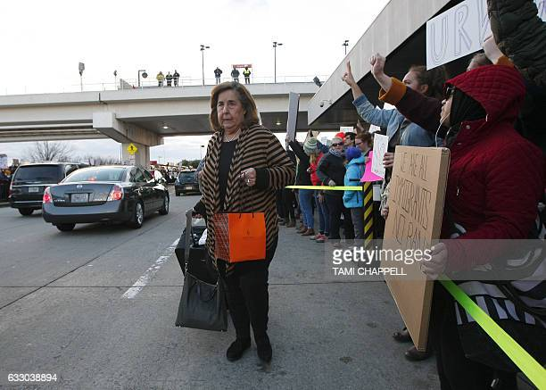 A traveler rolls her suitcase past protestors who crowded the sidewalks at HartsfieldJackson Atlanta International Airport to denounce US President...