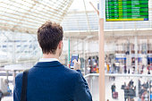 Traveler sending text message on smartphone with train timetable in background