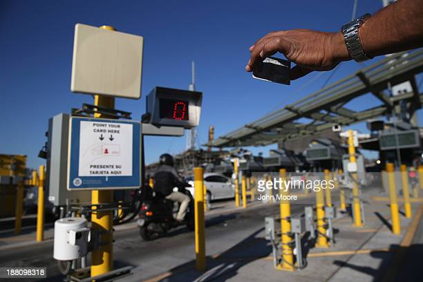 A traveler shows his ID to a radio frequency indentification reader while crossing from Mexico into the United States at the San Ysidro port of entry...