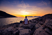 Traveler sits on the rock seashore and practicing yoga during sunset - adventure travel along Lycian way, Turkey. Back view,  wide angle.