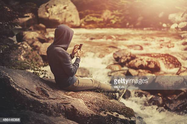 Traveler sitting on big stone with smartphone near mountain river