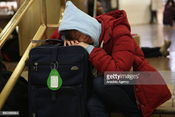 A traveler sleeps on her luggage after New York Port Authority was reopened after an explosion occured in Manhattan borough of New York City United...