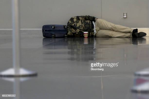 A traveler sleeps on the floor at John F Kennedy International Airport in New York US on Tuesday March 14 2017 A slight wobble in the path of a...