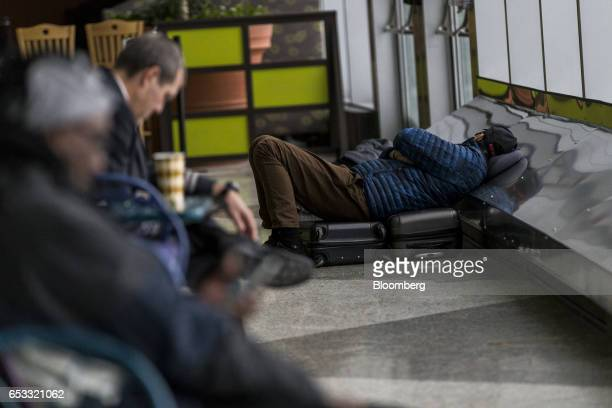 A traveler sleeps on the floor at LaGuardia Airport in New York US on Tuesday March 14 2017 A slight wobble in the path of a latewinter stormwill...