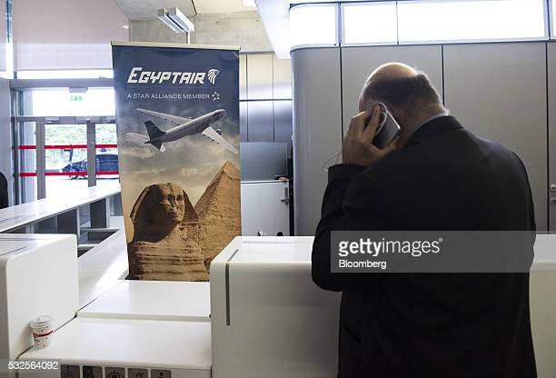 A traveler speaks on a mobile device beside the EgyptAir Airlines ticket office at Charles de Gaulle airport operated by Aeroports de Paris in Roissy...