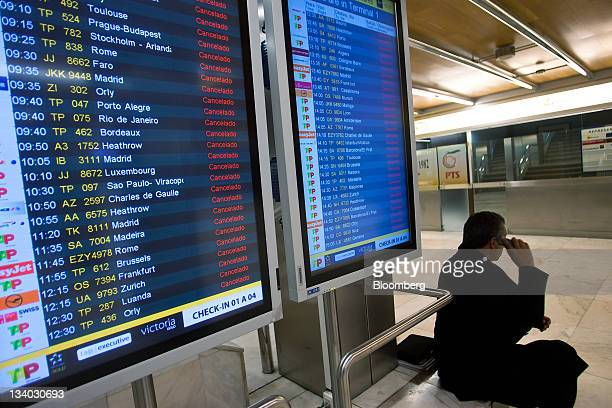 A traveler speaks on his mobile telephone next to a departures board displaying canceled flights at Lisbon airport during a general strike in Lisbon...