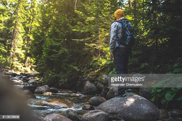 Traveler stands alone at the river in forest.