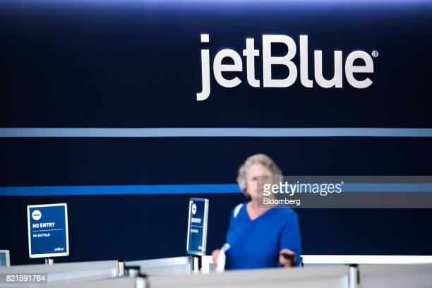 A traveler stands in front of JetBlue Airways Corp signage at Terminal 5 inside John F Kennedy International Airport in New York US on Wednesday July...