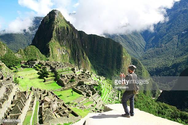 Traveler prendendo foto con il cellulare a Machu Picchu, Perù