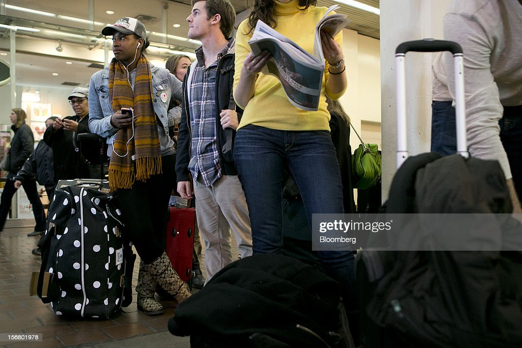 Traveler T'Keyah Slaten, left, waits to board an Amtrak train at Union Station in Washington, D.C., U.S., on Wednesday, Nov. 21, 2012. U.S. travel during the Thanksgiving holiday weekend will rise a fourth straight year, gaining 0.7 percent from 2011, as trips by automobile rise even as airplane trips decline, AAA said last week. Photographer: Andrew Harrer/Bloomberg