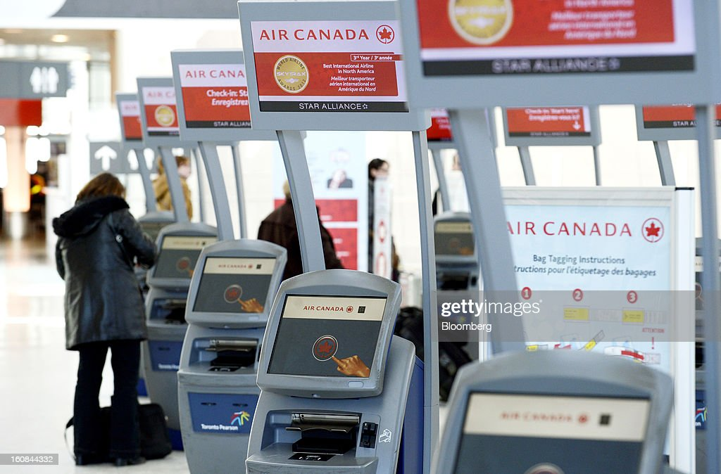 A traveler uses an Air Canada check-in kiosk at Pearson International Airport in Toronto, Ontario, Canada, on Wednesday, Feb. 6, 2013. Air Canada, the country's biggest carrier, is scheduled to announce quarterly earnings data on Feb. 7. Photographer: Aaron Harris/Bloomberg via Getty Images
