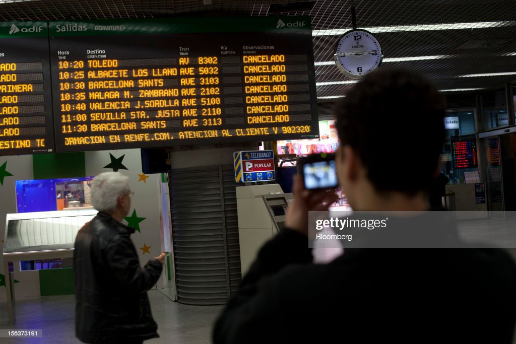 A traveler uses his mobile phone to take a photograph of the information board showing cancelled trains at Atocha railway station on the morning of a general strike in Madrid, Spain, on Wednesday, Nov. 14, 2012. Spanish unions today staged their second general strike against Prime Minister Mariano Rajoy as mounting opposition to budget cuts and bank bailouts undermines the 11-month-old government's ability to repair the economy. Photographer: Angel Navarrete/Bloomberg via Getty Images