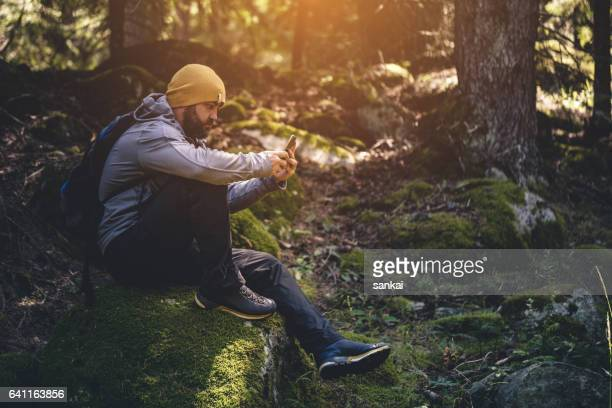 Traveler uses smartphone in the forest
