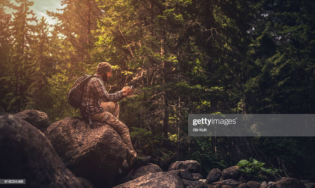 Traveler using a smart phone in the forest : Stock Photo