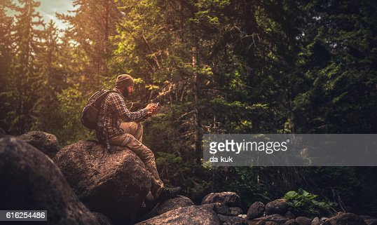 Traveler using a smart phone in the forest : Foto de stock