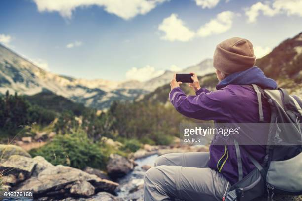 Traveler using a smartphone in the mountains