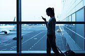 Silhouette of woman using her phone in the airport.