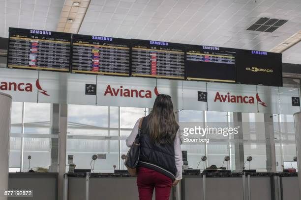 A traveler views monitors displaying the departure schedule for flights next to Avianca Holdings SA signage at El Dorado International Airport in...