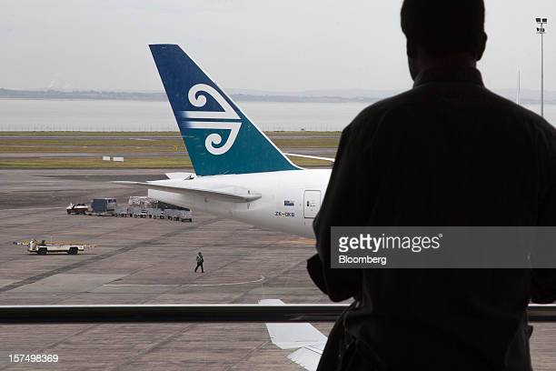 A traveler waits in a departure lounge as an Air New Zealand Ltd aircraft stands on the tarmac at Auckland International Airport in Auckland New...