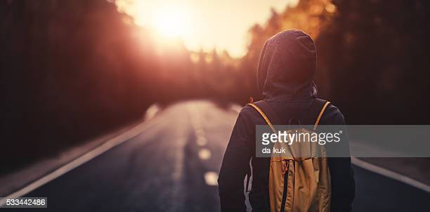 Traveler walking forward alone at sunset