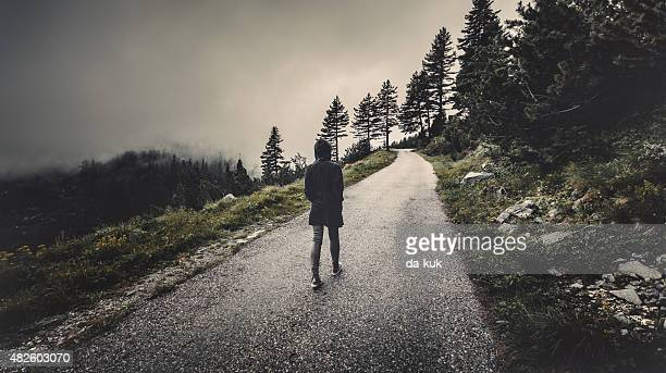 Traveler walking in a foggy forest at sunset