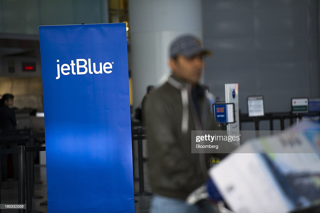A traveler walks past a JetBlue Airways Corp. check-in counter at San Francisco International Airport in San Francisco, California, U.S., on Monday, Jan. 28, 2013. JetBlue Airways Corp. fell the most in about two months after fourth-quarter profit tumbled 96 percent, more than analysts projected, as superstorm Sandy forced flight cancellations and reduced travel demand. Photographer: David Paul Morris/Bloomberg via Getty Images