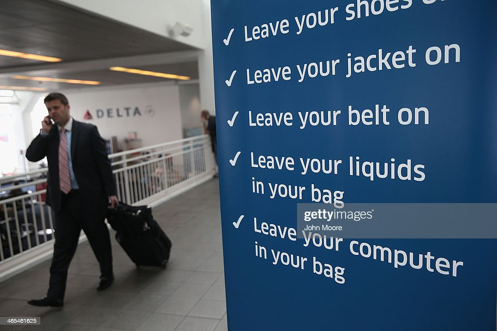 A traveler walks past a newly-opened TSA Pre-check application center at LaGuardia Airport on January 27, 2014 in New York City. Once approved, travelers can use special expidited Precheck security lanes. They can also leave on their shoes, light outerwear and belt, as well as keep their laptop and small containers of liquids inside carry-on luggage during security screening. The TSA plans to open more than 300 application centers across the country.