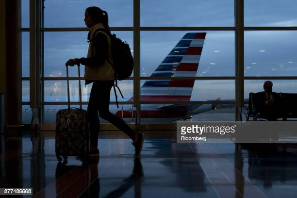 A traveler walks past an American Airlines Group Inc aircraft at Ronald Reagan National Airport in Washington DC US on Wednesday Nov 22 2017 The...
