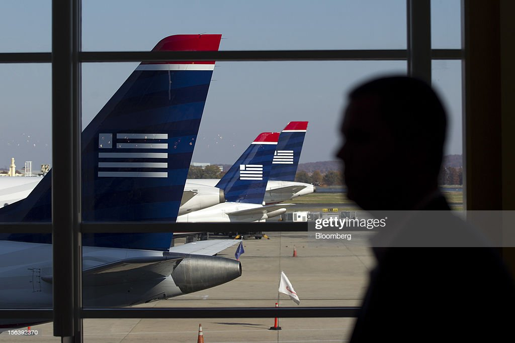 A traveler walks past US Airways Group Inc. airplanes on the tarmac prior to US Airways flight attendants picketing at Reagan National Airport in Washington, D.C., U.S., on Wednesday, Nov. 14, 2012. 6,700 flight attendants, represented by the Association of Flight Attendants-CWA (AFA), are currently taking a strike vote to demonstrate what they are willing to do to achieve a contract that can be ratified. Photographer: Andrew Harrer/Bloomberg via Getty Images