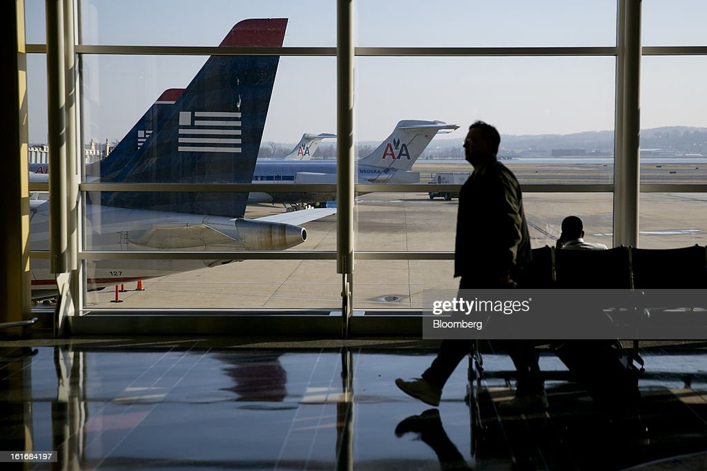 A traveler walks past US Airways Group Inc. and AMR Corp.'s American Airlines airplanes parked on the tarmac at Reagan National Airport in Washington, D.C., U.S., on Thursday, Feb. 14, 2013. US Airways Group Inc., spurned in three prior merger attempts, will combine with bankrupt AMR Corp.'s American Airlines in an $11 billion deal to create the world's largest carrier. Photographer: Andrew Harrer/Bloomberg via Getty Images