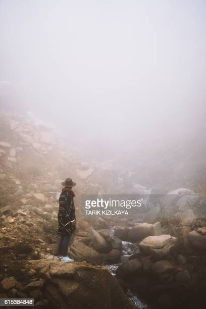 Traveler watching river running down the mountain