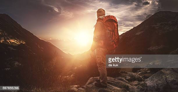 Traveler watching the sunset over the mountains