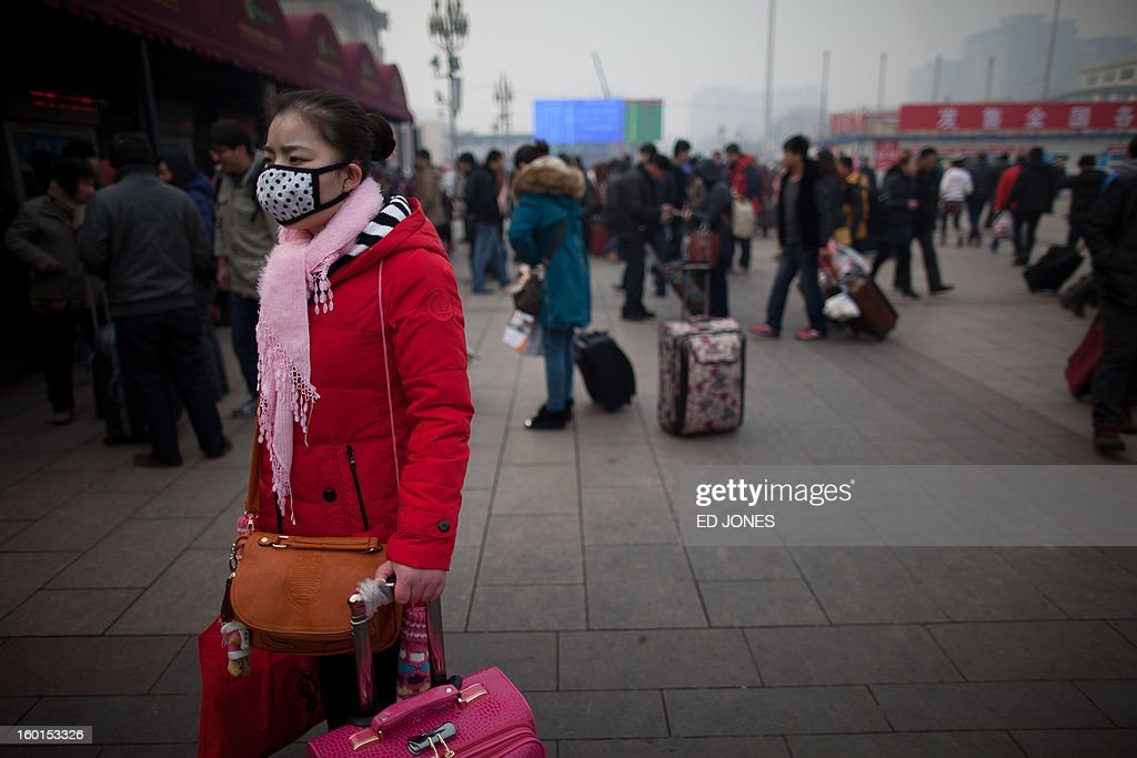 A traveler wears a mask as she stands with her luggage at Beijing Railway Station in Beijing on January 27, 2013. The world's largest annual migration began in China with tens of thousands in the capital boarding trains to journey home for next month's Lunar New Year celebrations. AFP PHOTO / Ed Jones