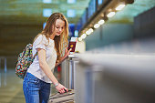 Beautiful young tourist girl with backpack and carry on luggage in international airport at check-in counter, giving her passport to an officer and waiting for her boarding pass