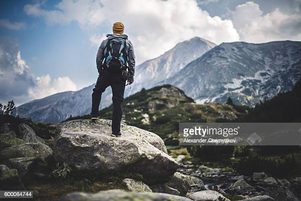 Traveler with backpack looks on a mountain peak
