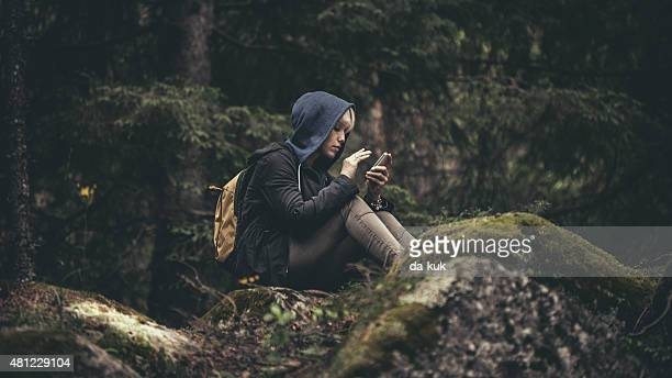 Traveler with backpack sitting in forest and holding a smartphone