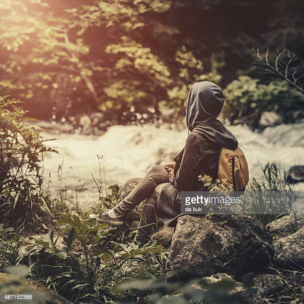 Traveler with backpack sitting in the forest