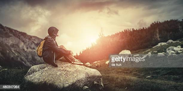 Traveler with backpack sitting on boulder in mountains at sunset