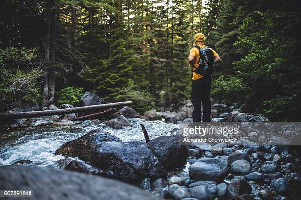 Traveler with backpack stands near river at forest