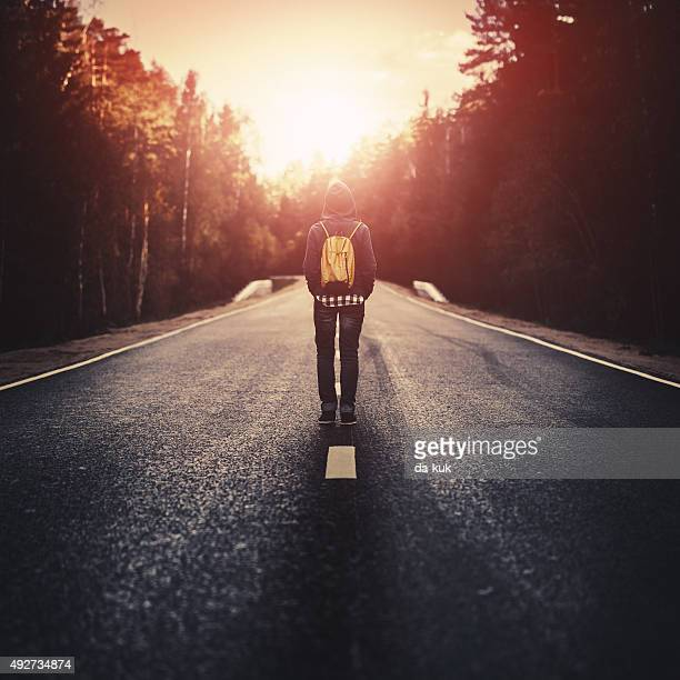 Traveler with backpack walking along the road