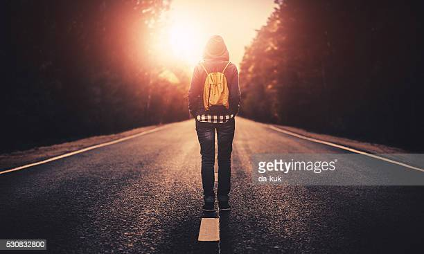 Traveler with backpack walking forward alone at sunset