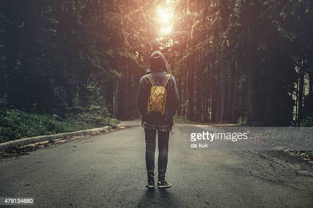 Traveler with backpack walking in a foggy forest at sunset